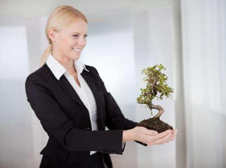 Portrait of beautiful young businesswoman holding Bonsai tree photo