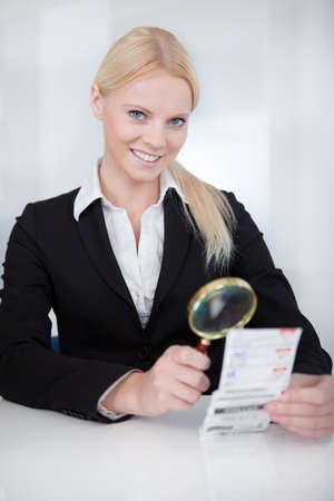 dinero falso: Alegre mujer de negocios que mira a través de cheque de la lupa