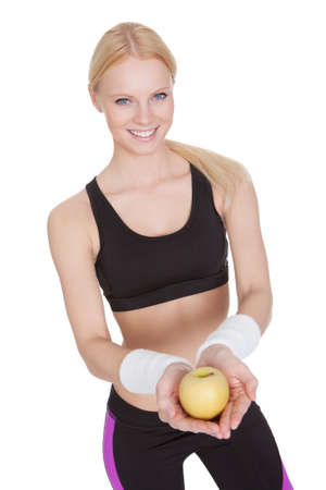 Beautiful young fitness woman holding apple. Isolated on white photo
