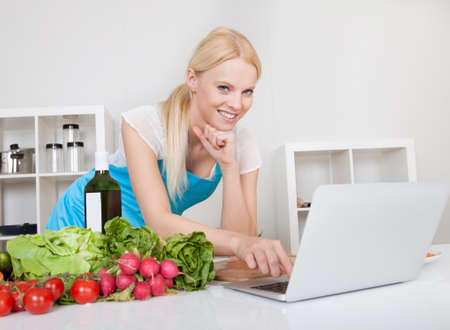 internet speed: Cheerful young woman cooking in the kitchen Stock Photo