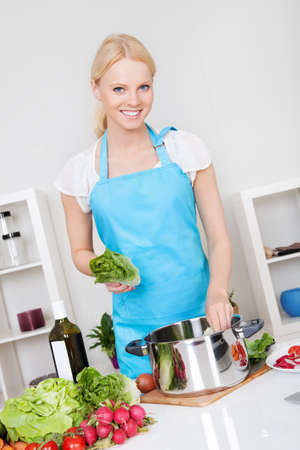 Cheerful young woman cooking in the kitchen photo