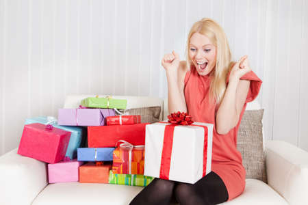 Beautiful young woman with her presents on the sofa photo