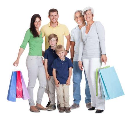 ni�os de compras: Generaciones de la familia feliz con bolsas de la compra. Aislados en blanco Foto de archivo