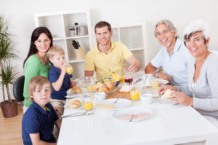 Happy generations family having breakfast together in the house photo