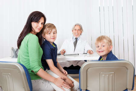 Mother and kids sitting at doctor office photo