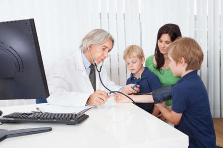 Doctor checking young kids at the office photo