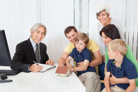 Family in real-estate agency talking construction planner photo