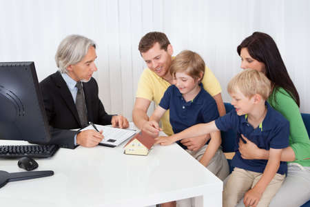 family planning: Family in real-estate agency talking construction planner