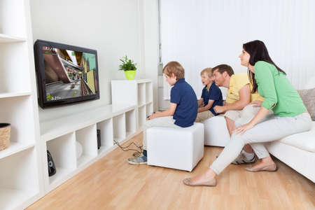 Young family having fun playing videogames at home photo