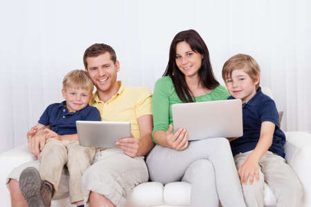 Happy family spending time together and using laptop at home photo