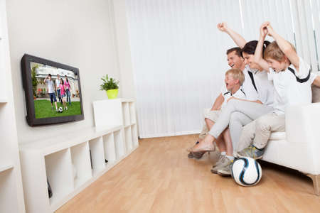 viendo television: Joven familia viendo el partido de fútbol en casa