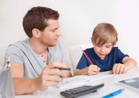 Young boy doing homework together with his father photo