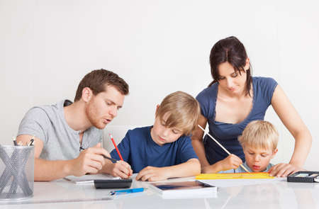 school notebook: Young family doing homework together at home Stock Photo
