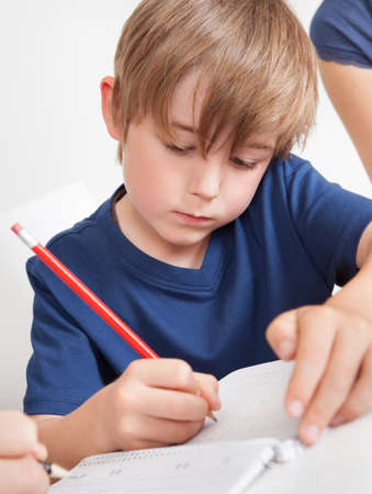 Portrait of young boy doing homework at home photo