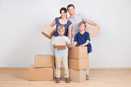 family moving house: Happy young family moving into new house