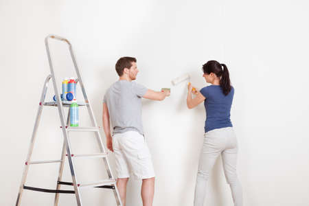 wall painting: Young couple painting wall together at home Stock Photo