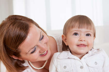 Adorable smiling little blonde girl with her doting mother posing for the camera Stock Photo - 15073313