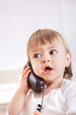 niños platicando: Pequeña niña escucha un teléfono pasado de moda en un teléfono con grandes ojos y la boca abierta en el temor
