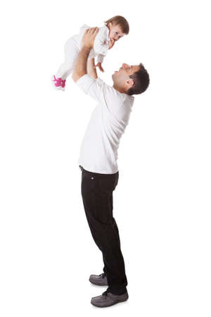 aloft: Young father playing with his small baby daughter holding her aloft with his arms extended above his head Stock Photo