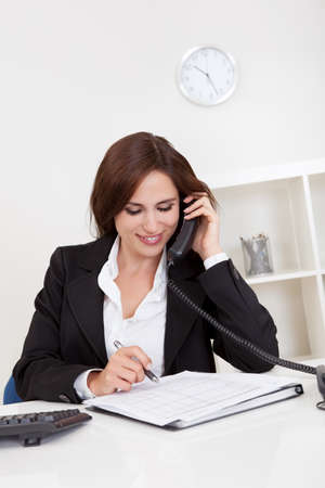 taking notes: Portrait of a beautiful young businesswoman calling on the phone