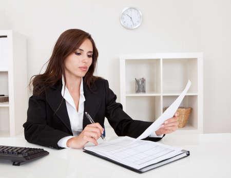 revisando documentos: Retrato de una mujer de negocios con los papeles en el escritorio de oficina