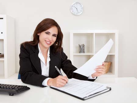 Portrait of a businesswoman with paperwork at office desk photo