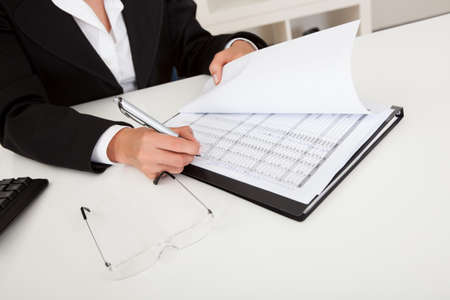 Midsection of a businesswoman with paperwork at office desk photo