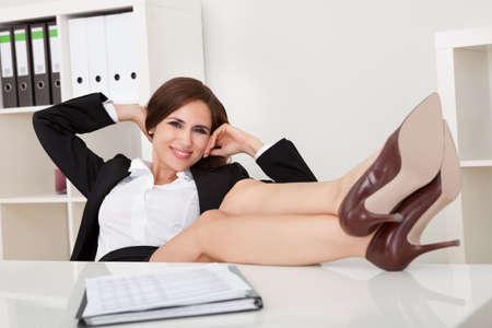female boss: Portrait der sch�nen weiblichen F�hrungskraft entspannt mit den F��en auf dem Schreibtisch im B�ro