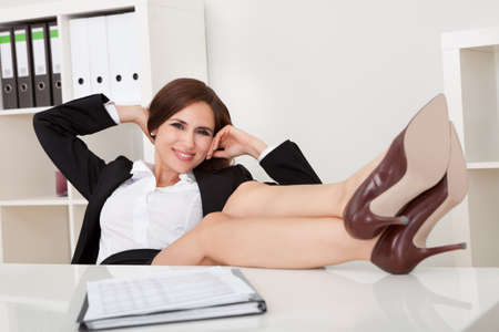 Portrait of beautiful female executive relaxing with feet on desk at office photo