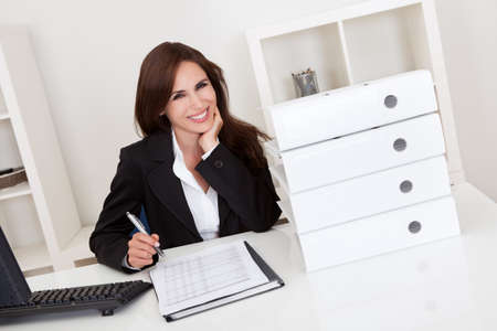 Portrait of a businesswoman with lots of paperwork at office desk Stock Photo - 15179574