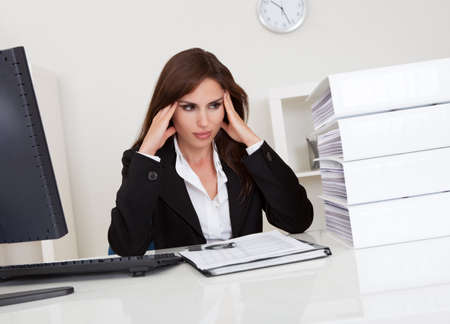 workaholic: Frustrated businesswoman with stack of folders on computer desk