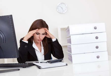 Frustrated businesswoman with stack of folders on computer desk photo