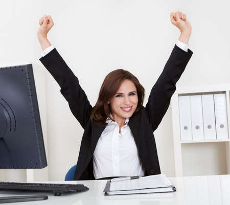 Portrait of a successful young businesswoman with clenched fists at computer desk Stock Photo - 15493583