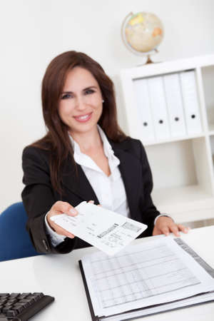 Portrait of a businesswoman offering secret envelop in office Stock Photo - 15493560