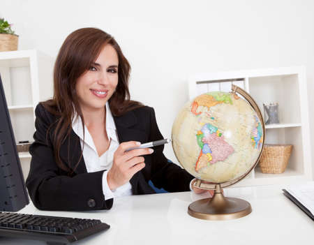 Portrait of a young businesswoman pointing at globe in office photo