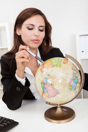 Portrait of a young businesswoman pointing at globe in office Stock Photo - 15179478