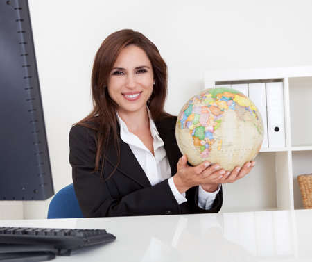Portrait of a young businesswoman holding a globe in office Stock Photo - 15493585
