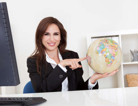 Portrait of a young businesswoman pointing at globe in office Stock Photo - 15493494