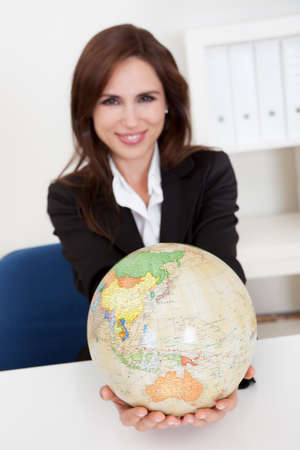 Portrait of a young businesswoman holding a globe in office photo