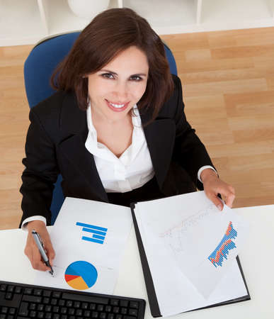 overhead view of a businesswoman working in office photo