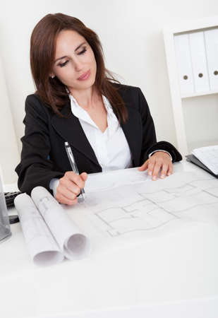 Female architect working with blueprints at office desk Stock Photo - 15179564