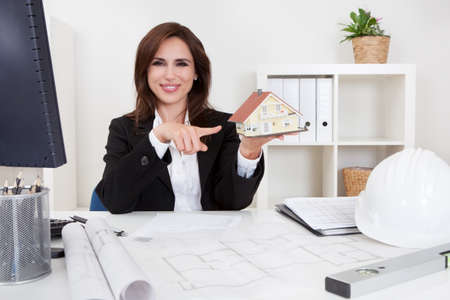female architect: Portrait of a businessman pointing at home model with blueprints on office desk