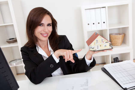 Portrait of a businessman pointing at home model with blueprints on office desk Stock Photo - 15179487
