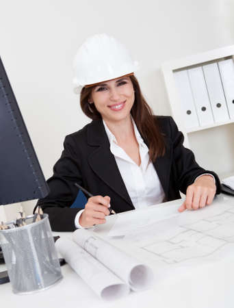 Portrait of young businesswoman wearing hardhat with blueprints at office desk Stock Photo - 15493547
