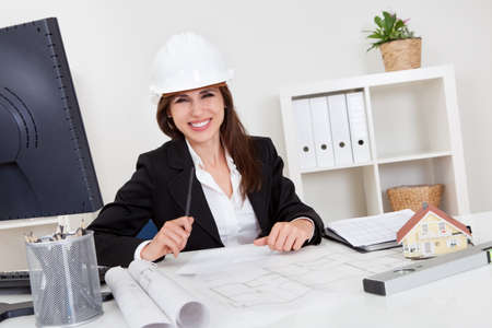 drawing table: Portrait of young businesswoman wearing hardhat with blueprints at office desk