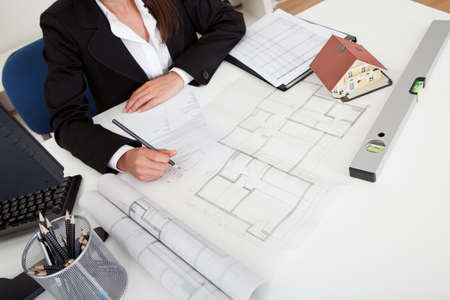 Midsection of female architect with model house, blueprints and spirit level on office desk photo