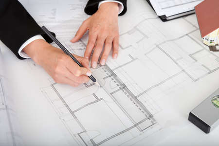 Midsection of female architect with model house, blueprints and spirit level on office desk Stock Photo - 15133213