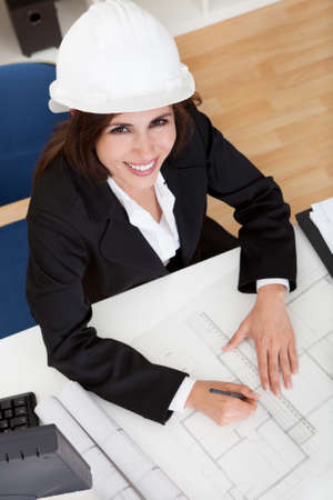 Portrait of young businesswoman wearing hardhat with blueprints at office desk photo