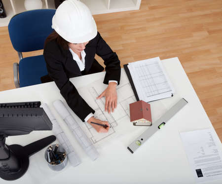 architect office: Portrait of young businesswoman wearing hardhat with blueprints at office desk