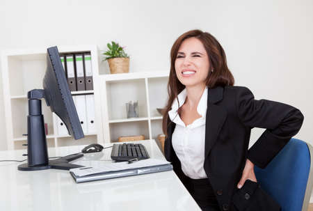 aches: Young businesswoman having back pain while sitting at office desk Stock Photo
